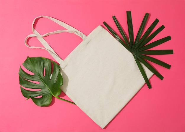 Borsa e foglie di palma di eco sul fondo di colore