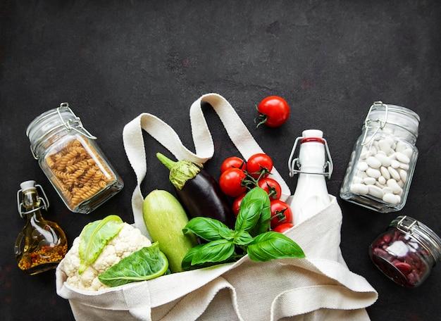 Borsa ecologica con frutta e verdura, vasetti in vetro con fagioli e pasta