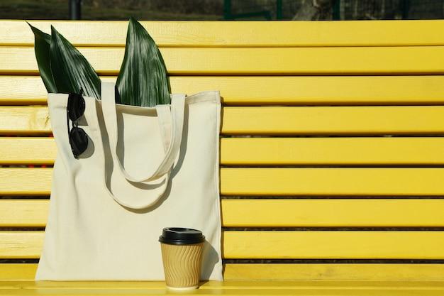 Borsa ecologica con foglie, occhiali da sole e bicchiere di carta su panca da esterno