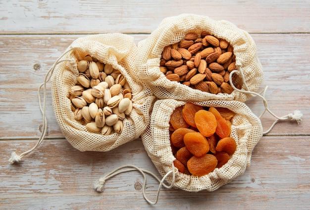 Sacchetti ecologici con pistacchi, mandorle e albicocche secche su una superficie di legno