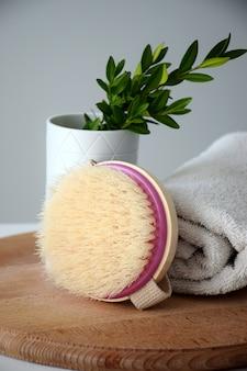 Spazzola per il corpo eco per massaggio a secco e asciugamano bianco su tavola rotonda di legno