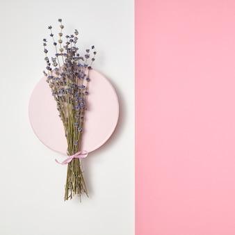 Eco ramo di fiori di lavanda su una tavola rotonda in ceramica su una parete pastello bicromia, copia dello spazio. vista dall'alto.
