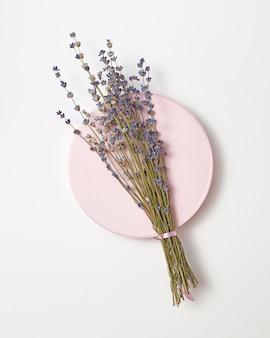 Eco ramo di fiori di lavanda su una tavola rotonda in ceramica su un muro grigio chiaro, copia dello spazio. vista dall'alto.