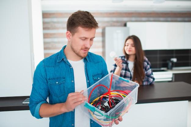 Concetto di eco. protezione ambientale. la famiglia sta selezionando i vecchi dispositivi elettrici domestici. vetro, lampadine, ferro, gomma, metallo, batterie e fili devono essere riciclati. responsabilmente proteggere la natura