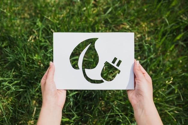 Concetto di eco con le mani che tengono carta tagliata che mostra energia di eco