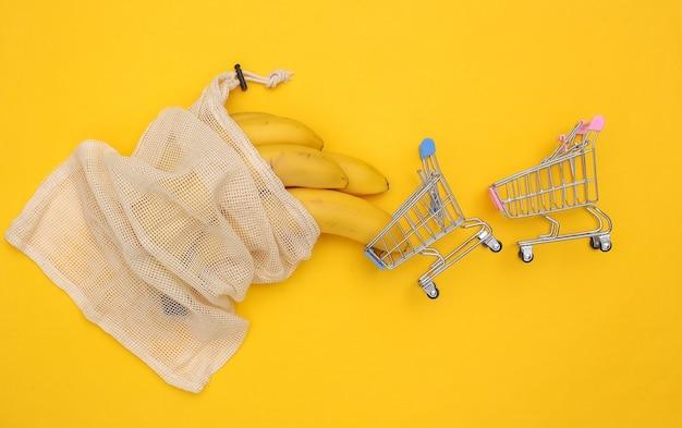 Borsa in cotone ecologico con banane mature e mini carrelli della spesa su sfondo giallo.
