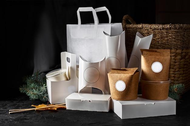 Stoviglie in carta ecologica. bicchieri di carta, piatti, borsa, contenitori per fast food, scatola per consegna cibo e posate in legno su sfondo nero. concetto di riciclaggio.