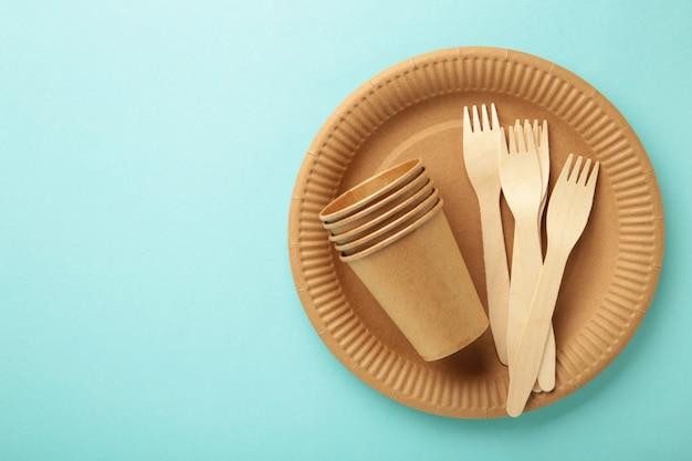 Stoviglie in carta ecologica. bicchieri di carta, piatti, borsa, contenitori per fast food e posate in legno su sfondo blu. zero sprechi. concetto di riciclaggio. copia spazio