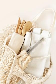 Accessori ecologici: posate di bambù, borsa ecologica, cannucce di metallo riutilizzabili. zero rifiuti, concetto senza plastica, stile di vita sostenibile. vista dall'alto, piatto.