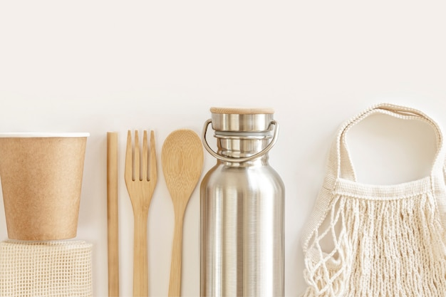 Accessori ecologici: posate in bambù, borsa ecologica, bottiglia d'acqua riutilizzabile. zero rifiuti, concetto senza plastica, stile di vita sostenibile. vista dall'alto, piatto.