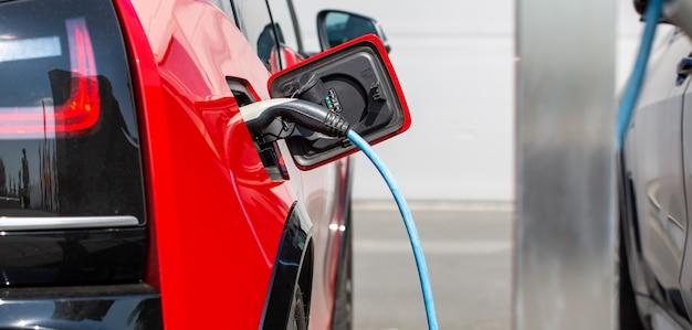 Concetto di energia alternativa ecologico, ricarica automatica di auto elettriche alla stazione di ricarica, veicoli energetici