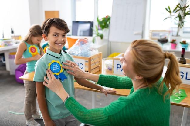 Premio ecologico. splendido scolaro raggiante che si sente fantastico ricevere un premio ecologico a scuola