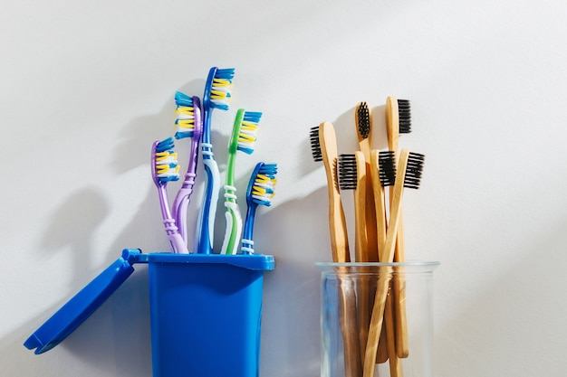 Spazzolini da denti in bambù ecologici in vetro e spazzolini da denti in plastica nel cestino.