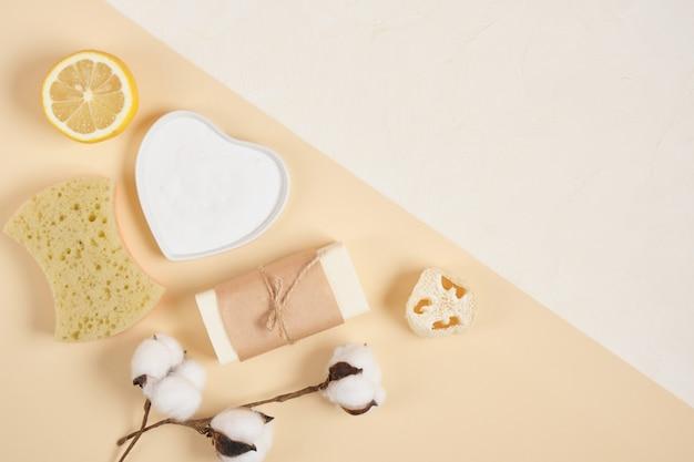 Kit ecologico per la pulizia e la cura del corpo, limone, sapone, soda, luffa, spugna e fiore di cotone su sfondo beige, concetto di stile di vita zero rifiuti vista dall'alto spazio copia