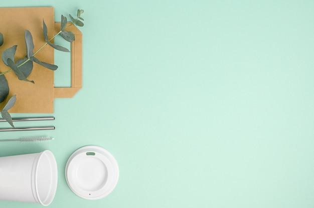 Modello di caffè ecologico per design, cannucce, sacchetto di carta marrone, etichetta, cappuccio, spazio di copia su verde, rifiuti zero