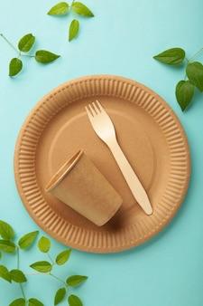 Piatti usa e getta ecologici con foglie verdi su sfondo blu. zero sprechi, eco friendly, sfondo senza plastica. foto verticale