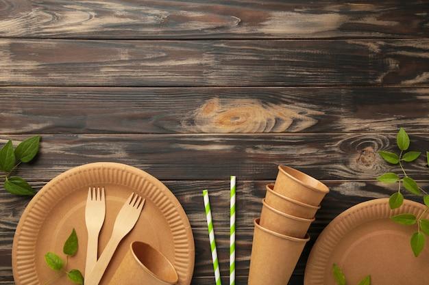 Piatti usa e getta ecologici con foglie verdi su sfondo marrone. zero sprechi, eco friendly, sfondo senza plastica. vista dall'alto