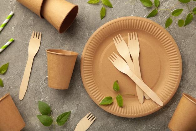 Piatti usa e getta ecologici con foglie verdi su sfondo grigio. zero sprechi, eco friendly, sfondo senza plastica.