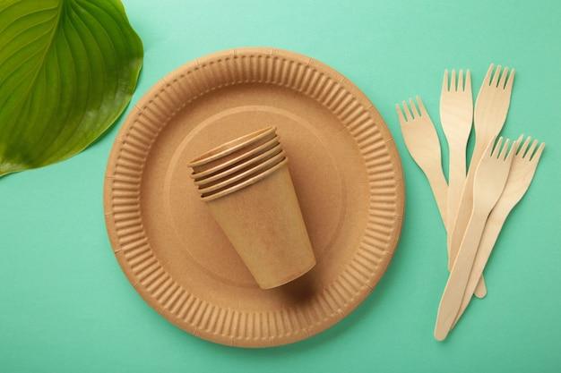 Piatti usa e getta ecologici con foglie verdi su sfondo menta. zero sprechi, eco friendly, sfondo senza plastica. foto verticale