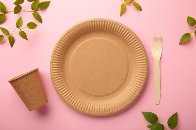 Piatti usa e getta ecologici con foglie verdi su sfondo rosa. zero sprechi, eco friendly, sfondo senza plastica. vista dall'alto
