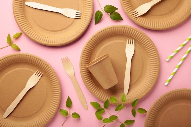 Piatti usa e getta ecologici con foglie verdi su sfondo rosa. zero sprechi, eco friendly, sfondo senza plastica. foto verticale