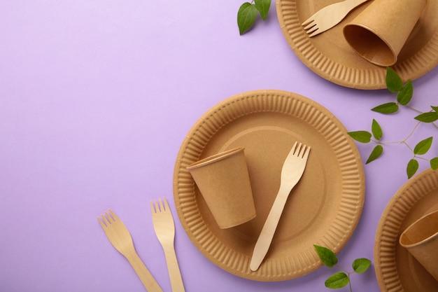 Piatti usa e getta ecologici con foglie verdi su sfondo viola. zero sprechi, eco friendly, sfondo senza plastica.