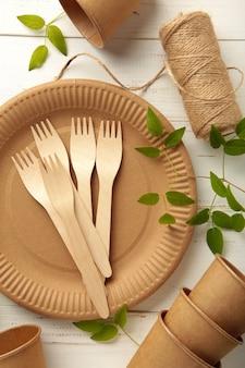 Piatti usa e getta ecologici con foglie verdi su sfondo bianco. sfondo senza plastica.