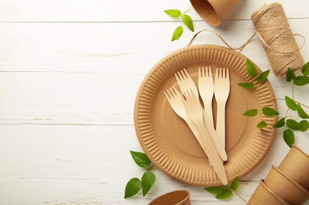 Piatti usa e getta ecologici con foglie verdi su sfondo bianco. zero sprechi, eco friendly, sfondo senza plastica. vista dall'alto