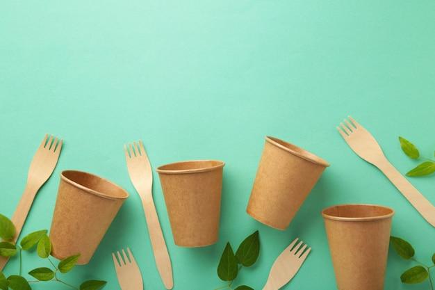 Bicchieri usa e getta ecologici e forchetta con foglie verdi su sfondo menta. zero sprechi, eco friendly, sfondo senza plastica.