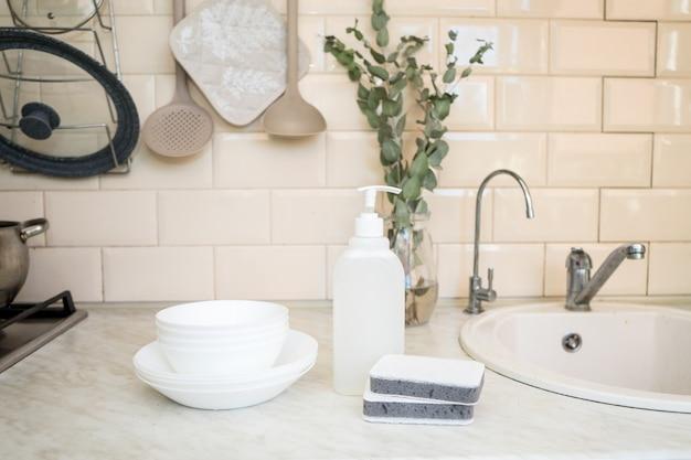 Sapone per piatti non tossico ecologico con fiori di camomilla puliti piatti bianchi