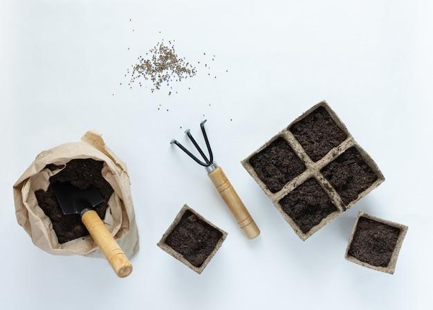 Vasi ecologici per piantine e semi su sfondo bianco, sacchetto con spatola e rastrelli per terra e giardino