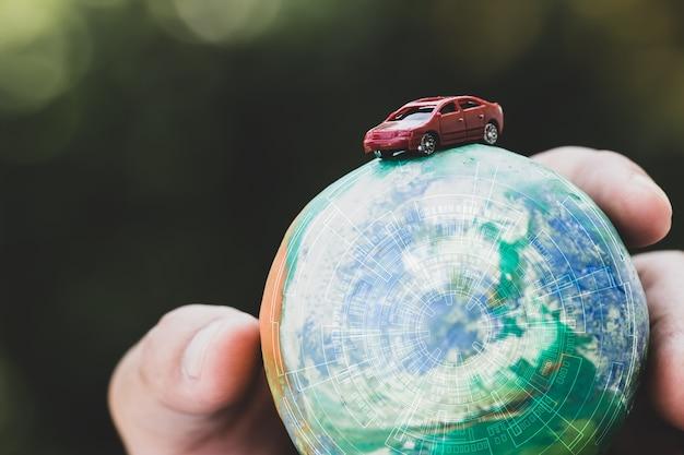 Eco friendly salva il concetto del mondo. automobile rossa e mani che tengono l'argilla del globo di modello con il radar sfondo naturale. idee di manutenzione della terra riducendo il consumo di energia, viaggia in tutto il mondo