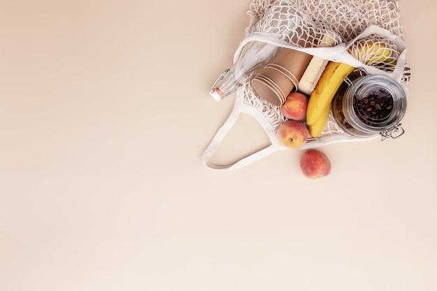 Concetto estivo ecologico su sfondo beige con frutta eco shopping bag