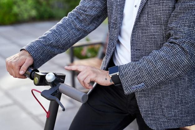 Veicolo ecologico primo piano di un elegante uomo d'affari di mezza età che utilizza uno scooter elettrico in piedi