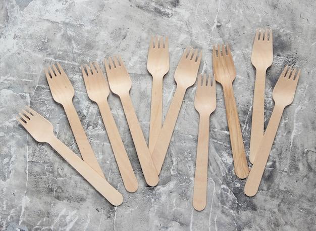 Forchette di legno ecologiche su sfondo grigio cemento.