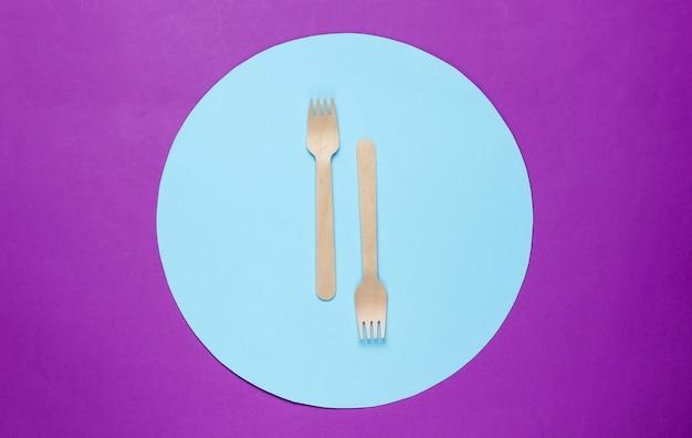 Forchette di legno eco friendly su sfondo viola con cerchio blu.