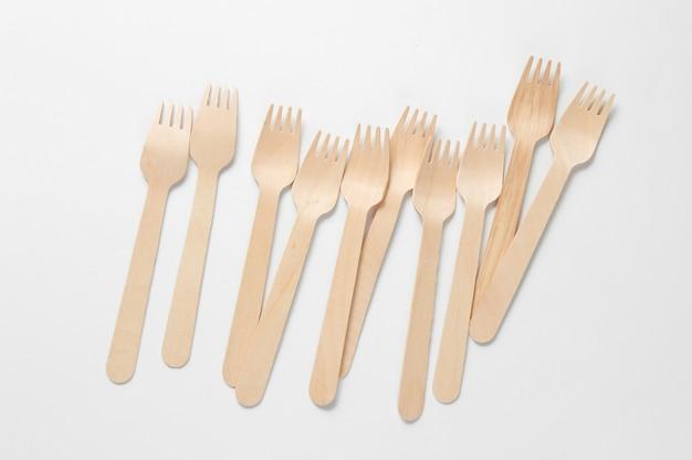 Forchette di legno ecologiche su uno sfondo bianco. concetto di eco minimalista