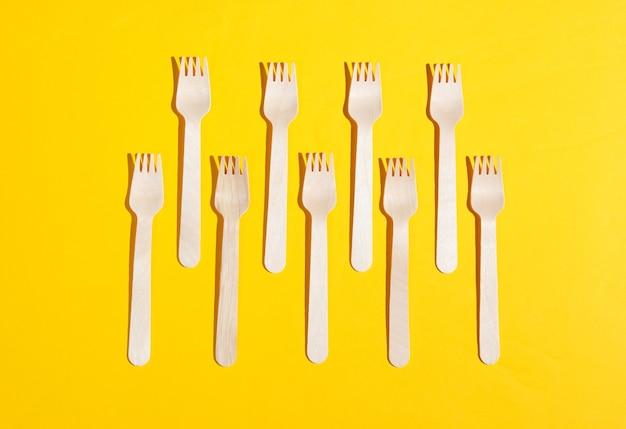 Forchette di legno ecologiche su sfondo giallo. concetto di eco minimalista.