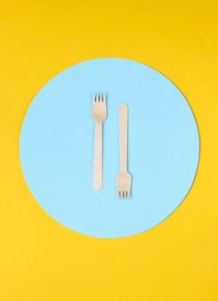 Forchette di legno ecologiche su sfondo giallo con cerchio blu.