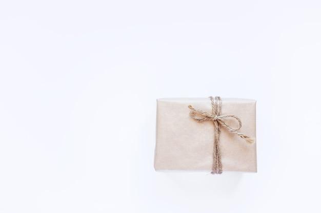 Confezione regalo ecologica in carta kraft su sfondo bianco isolato. stile naturale ecologico vintage. composizione vista dall'alto, flatlay per le vacanze di capodanno, spazio copia
