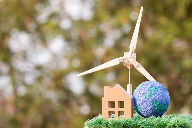 Eco green energy/future energia alternativa o consapevolezza del concetto di ambiente: turbina eolica / mulino a vento con casa, modello di terra globale. idea su una casa familiare residenziale sostenibile, usa l'ecologia rinnovabile
