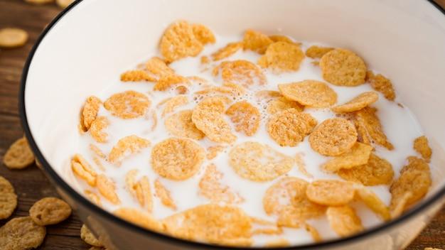 Sfondo di cibo sano eco. fiocchi di mais con latte. fiocchi di latte in una ciotola bianca. cibo sano e colazione fresca
