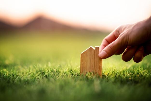 Concetto della casa di eco, mano che tiene piccolo modello della casa sopra erba verde.