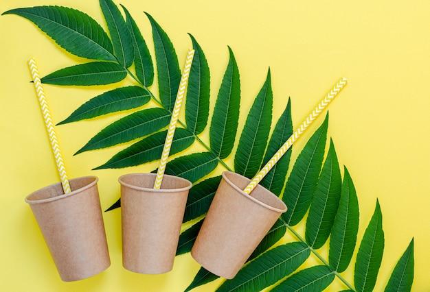 Bicchieri di carta ecologici con cannucce e foglie verdi su sfondo giallo. stile di vita senza plastica