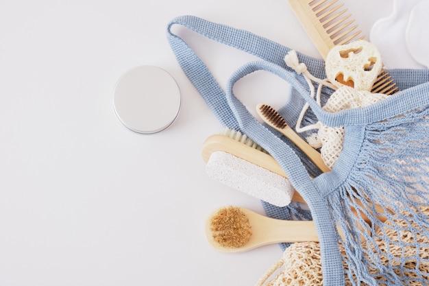 Eco set per la cura del corpo in borsa a maglia su sfondo grigio, cosmetici naturali e stile di vita a rifiuti zero, prodotti per la cura della pelle in legno