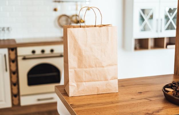 Eco shopping bag di carta sul tavolo in cucina moderna. consegna del cibo o concetto di acquisto del mercato.