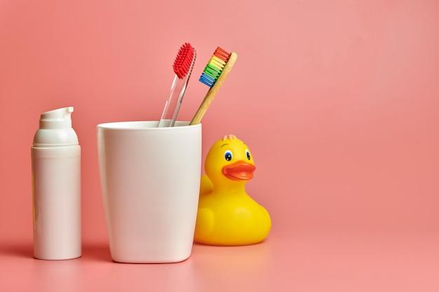 Spazzolini ecologici in bicchiere di plastica con anatra giocattolo e crema per il viso