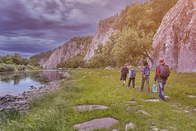 Eco-turismo, escursionisti di gruppo che camminano sul sentiero lungo il fiume, in un selvaggio terreno roccioso.