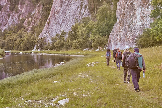 Eco-turismo in zona montuosa, gruppo di cinque escursionisti che camminano su sentiero forestale lungo il fiume con coste rocciose.
