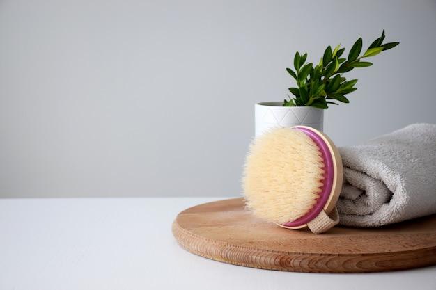 Spazzola per il corpo in legno eco, contenitore con pianta e asciugamano bianco su tavola rotonda in legno